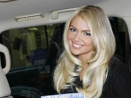 A candid Kate Upton smiling and holding a copy of her cover of Sports Illustrated.